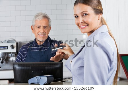 Portrait of mid adult woman giving credit card to male cashier at cash counter