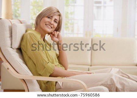 Portrait of mid-adult woman smiling at camera sitting in armchair in bright living room with hand up at face.?