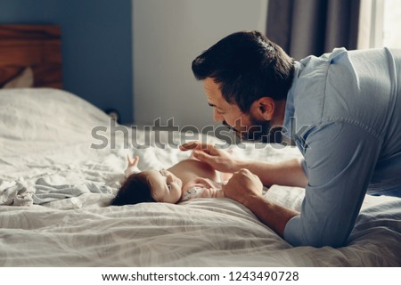 Portrait of middle age Caucasian father talking to newborn baby son daughter. Male man parent smiling to child on bed in bedroom at home. Authentic lifestyle real candid moment.
