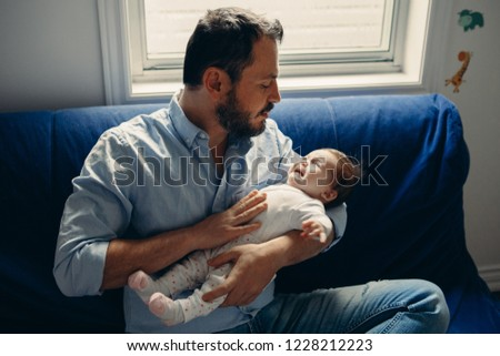 Portrait of middle age Caucasian father trying to calm down newborn baby. Male man parent holding child on his hands. Authentic lifestyle documenatry moment. Single dad family life concept.