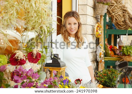 Portrait of middle age flower shop owner standing in front of flower shop. Small business.