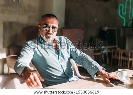 Portrait of middle age man with beard and with sunglasses looking confidant, like a boss. Business people
