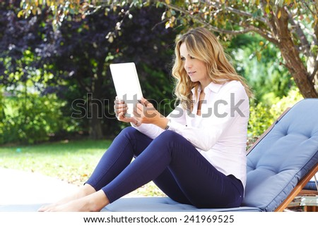 Portrait of middle age mother sitting at garden at home while using personal banking at digital tablet.