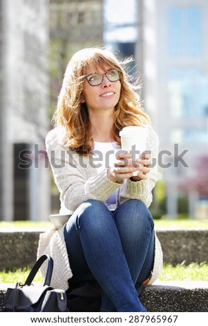 Portrait of middle age professional woman sitting at office park while drinking coffee and looking up.