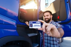 Portrait of middle aged bearded truck driver standing by the truck and showing his commercial driver license. Focus on CDL license. Truck driving school and job openings.