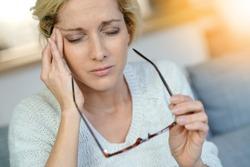 Portrait of middle-aged blond woman having a migraine