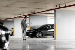 Portrait of middle-aged businessman leaving his black car in a parking garage. Horizontal shot