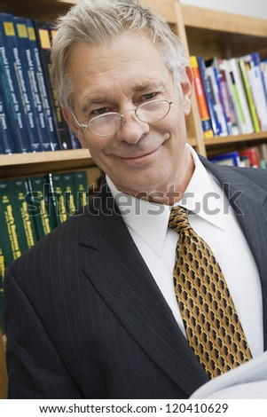 Portrait of middle aged businessman smiling while standing in library