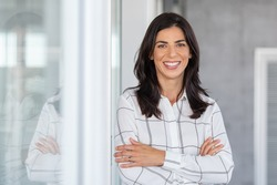 Portrait of middle aged businesswoman in modern office looking at camera. Confident business woman with arms crossed standing while leaning against glass wall. Proud woman smiling in with copy space.