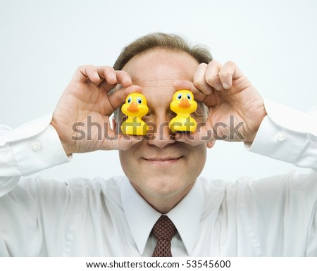 Portrait of middle aged  Caucasian businessman holding rubber ducks up to face.