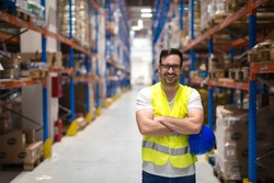 Portrait of middle aged caucasian warehouse worker standing in large warehouse distribution center with arms crossed. In background shelves with goods. Worker smilling and looking to the camera.