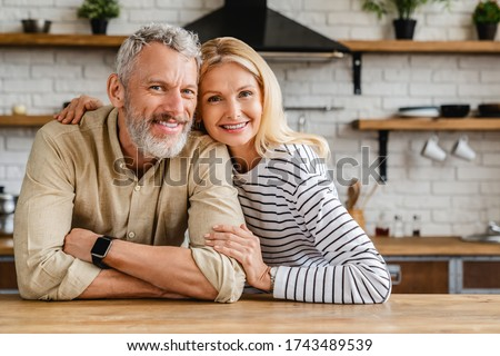 Portrait of middle aged couple hugging while standing together in kitchen at home Stockfoto ©