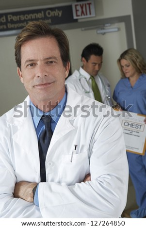 Portrait of middle aged doctor standing arms crossed with colleagues discussing in background