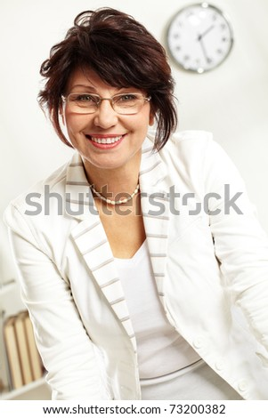 Portrait of middle-aged female looking at camera with smile - stock photo