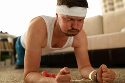 Portrait of middle aged man making funny face while training at home. Person in sportswear doing exercise on carpet. Indoors sport on quarantine and hobby concept