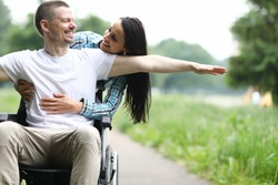 Portrait of middle-aged man sitting in wheelchair and smiling. Beautiful female hugging male from behind. Cheerful and happy couple outdoors. Disabled people concept