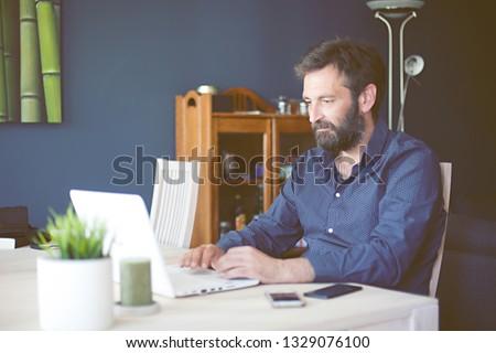 Portrait of middle aged man working in home office looking at his laptop