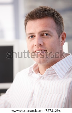 Portrait of middle-aged office worker smiling in office.?