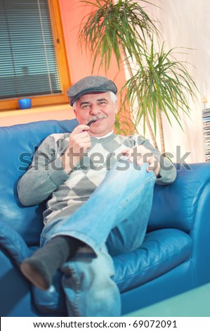 Portrait of middle-aged smiling man with relaxing at home with a tobacco pipe