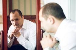 portrait of middle aged stressed man watching himself in the mirror