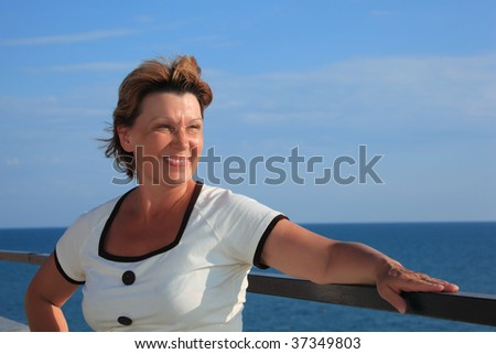 portrait of middle-aged woman on balcony over sea