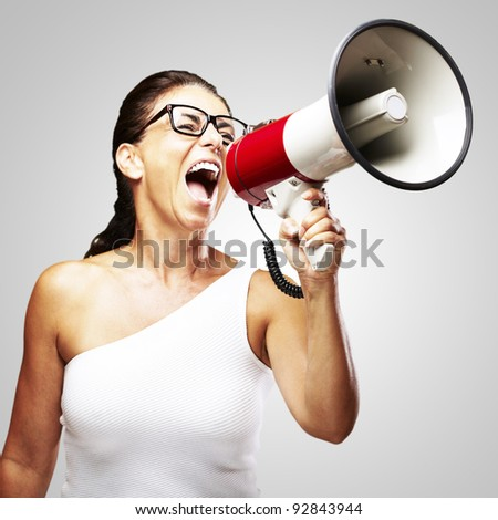 portrait of middle aged woman shouting using megaphone over grey background