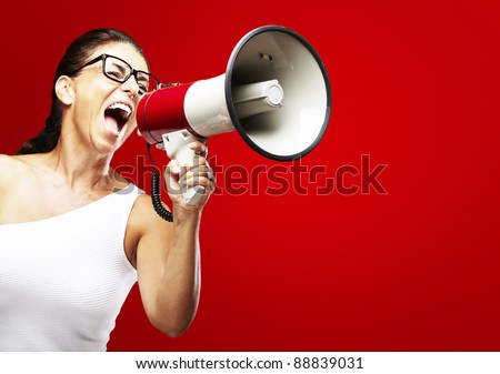 portrait of middle aged woman shouting using megaphone over red background