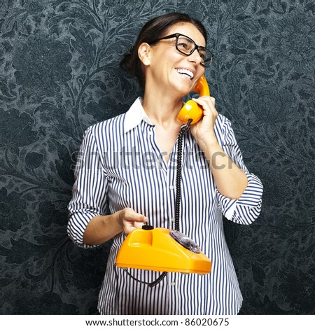 portrait of middle aged woman talking on vintage telephone against a grunge background