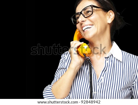 portrait of middle aged woman wearing glasses with vintage telephone on black background