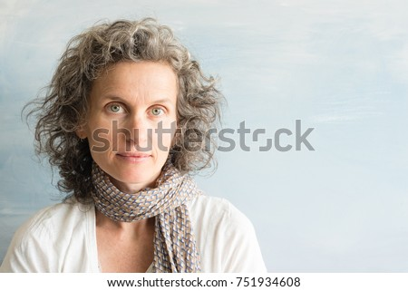 Portrait of middle aged woman with wavy grey hair and scarf against blue background (selective focus) Photo stock ©