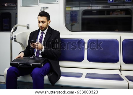 Shutterstock Portrait of Middle-Eastern businessman commuting to work in subway train, using smartphone to listen to music