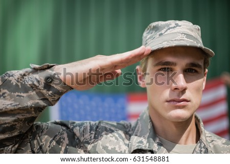Portrait of military soldier giving salute in boot camp