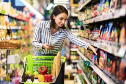 Portrait Of Millennial Lady Holding And Using Smartphone Buying Food Groceries Walking In Supermarket With Trolley Cart. Female Customer Shopping With Checklist, Taking Products From Shelf At The Shop
