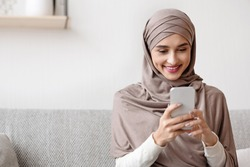 Portrait of millennial muslim girl in hijab using smartphone at home, messaging or browsing social networks, sitting on sofa in living room
