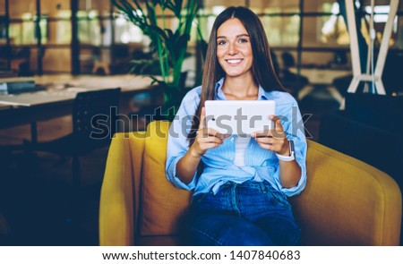 Portrait of millennial smiling hipster girl using touch pad for chatting during free time in loft interior, young successful woman looking at camera and enjoying free time with modern technology
