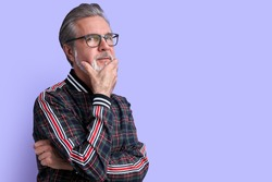 portrait of minded pensive curious old man in contemplation, have spectacles touch chin isolated over purple background, look at camera