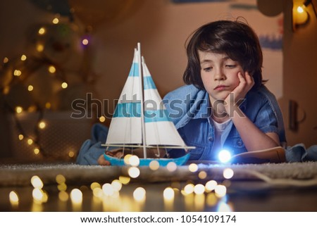 Portrait of mirthless boy playing on the floor in cozy children room. He propping up chin and looking with sadness at ship