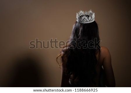 Portrait of Miss Pageant Beauty Contest in open back Evening fur Gown dress with sparkle light Diamond Crown, Asian Woman fashion make up black hair style, turn back side rear view no face #1188666925