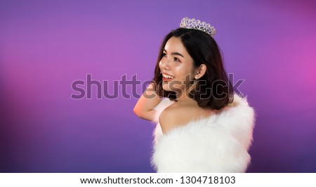 Portrait of Miss Pageant Beauty Contest in white fur Evening dress light Diamond Crown, LGBT transgender Asian Woman fashion make up black hair style, studio lighting gradient shade purple background #1304718103