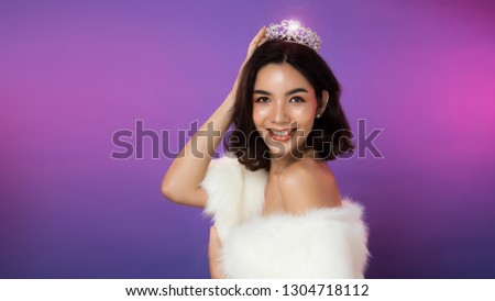 Portrait of Miss Pageant Beauty Contest in white fur Evening dress light Diamond Crown, LGBT transgender Asian Woman fashion make up black hair style, studio lighting gradient shade purple background #1304718112