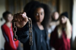 Portrait of mixed-race teenager girl with chain indoors in abandoned building.