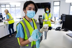 Portrait of mixed race woman wearing hi vis vest, gloves and face mask sanitizing office with disinfectant, colleagues in the background. Hygiene in workplace during Coronavirus Covid 19 pandemic.