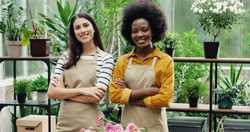 Portrait of mixed-races beautiful women florists standing in own floral shop and smiling to camera. Caucasian and African American females business partners working in flower store. Business concept