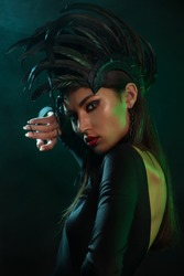 Portrait of Model in a headdress  with feathers. Сoncept for rock musicians or music festival or Halloween party. Dark background, studio