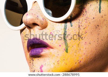 Portrait of model wearing sunglasses. Close-up portrait of young woman with unusual makeup. Model posing with paint drops over her face. Creative makeup.