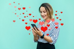 Portrait of modern attractive middle aged stylish woman holding mobile smart phone and looking, toothy smile. Valentine day or online dating concept. Red hearts flying out smartphone in woman hands.