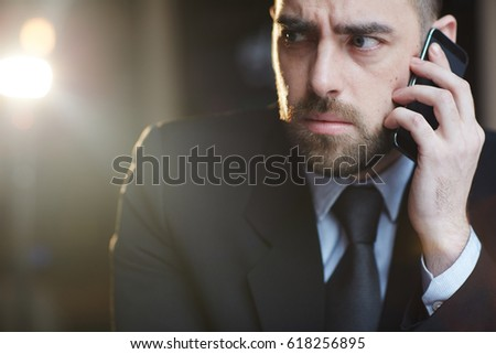 Portrait of modern bearded businessman looking confused and troubled while talking by mobile phone with problem client against black lens flare background #618256895