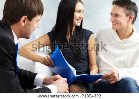 Portrait of modern couple discussing mortgage conditions with real estate agent near by