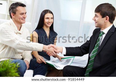 Portrait of modern couple making a deal with real estate manager