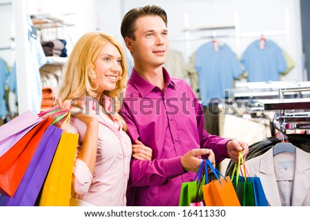 Portrait of modern couple with shopping bags looking at clothes in the trade center